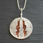 Textured and handcut sterling silver backed with red wood. $125.